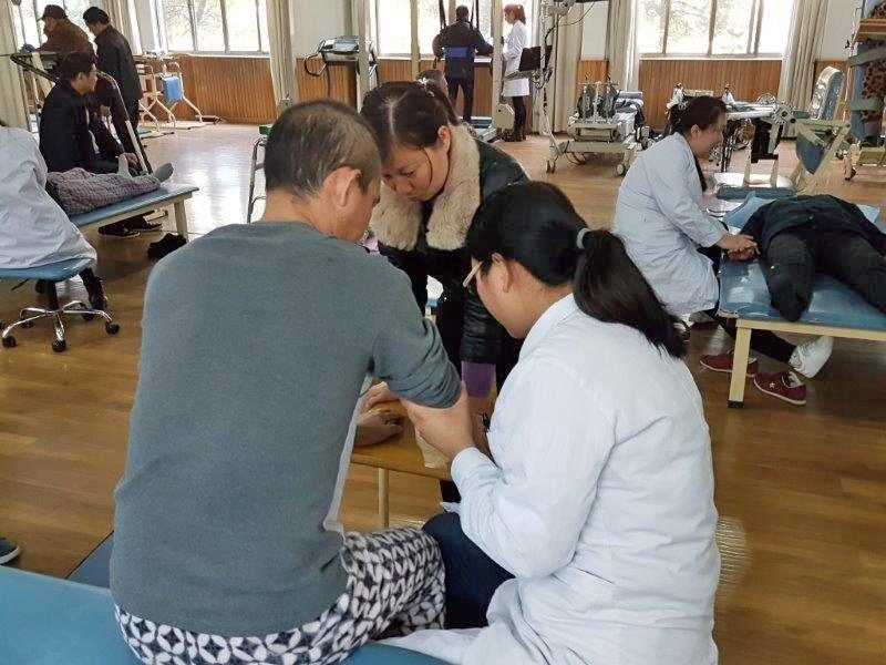 Die chinesischen Kollegen mit den Patienten im Behandlungsraum